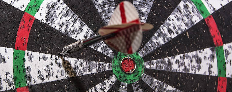 An example of a dart left in a paper dartboard.