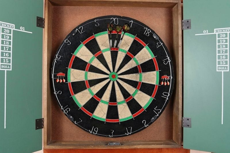 A dartboard cabinet with a steel tip dartboard and scoreboard.